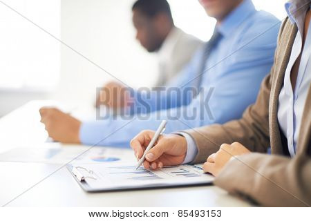 Row of people making notes on spreadsheet