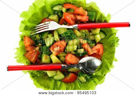 Salad of tomatoes, cucumbers and dill on lettuce leaves with a spoon and fork