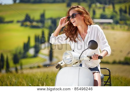 Young beautiful italian woman sitting on a italian scooter in Italy hills