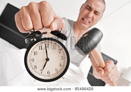 a young man  in bed about to hammer his alarm clock at seven in the morning