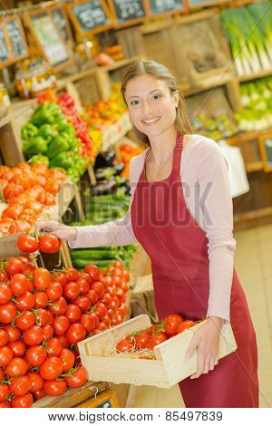 Shop worker carrying a crate of tomatoes