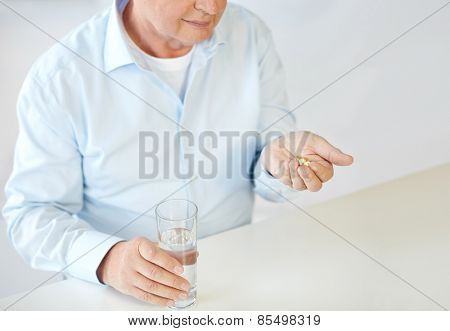oldness, medicine, health care and people concept - close up of old man with pills and water glass