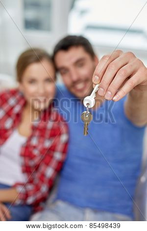 people, real estate, home and family concept - close up of happy couple showing key at at home