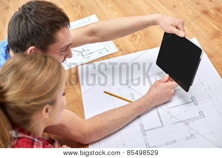 repair, building, renovation, architecture and technology concept - close up of couple with tablet pc computer blank screen and blueprints at home