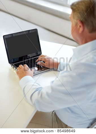 technology, business, retirement, people and leisure concept - close up of senior man with laptop computer typing at table in office