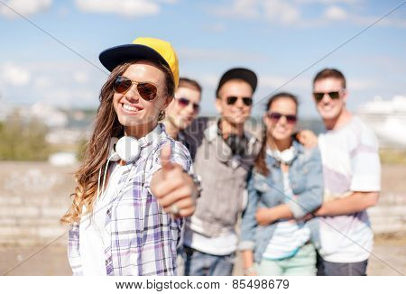 summer holidays and teenage concept - teenage girl in sunglasses, cap and headphones hanging out with friends outside and showing thumbs up