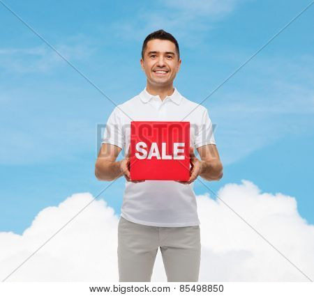 shopping, consumerism, discount and people concept - smiling man with red sale sigh over blue sky and cloud background