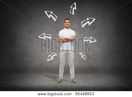choice, direction, possibilities and people concept - smiling man in white t-shirt with crossed arms over arrow doodles and concrete background