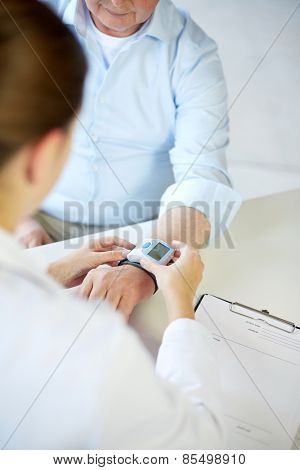 healthcare, oldness, cardiology and medicine concept - close up of doctor measuring pulse or blood pressure with wrist tonometer to senior man in hospital