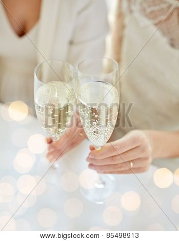 people, homosexuality, same-sex marriage, celebration and love concept - close up of happy married lesbian couple hands holding and clinking champagne glasses over holiday lights background