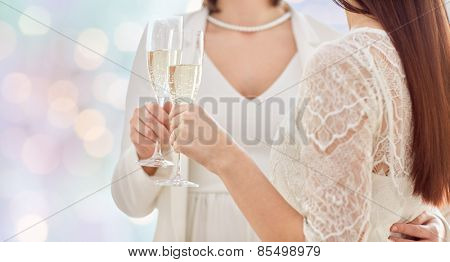 people, homosexuality, same-sex marriage, celebration and love concept - close up of happy married lesbian couple holding and clinking champagne glasses over holiday lights background