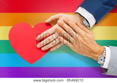 people, homosexuality, same-sex marriage, valentines day and love concept - close up of happy married male gay couple hands with red paper heart shape over rainbow flag background