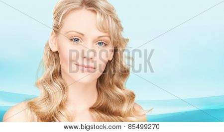 beauty, people, hair care and health concept - beautiful young woman face with long wavy hair over blue background
