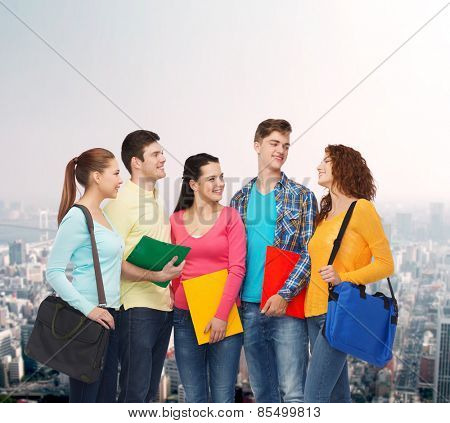 friendship, education and people concept - group of smiling teenagers with folders and school bags over city background