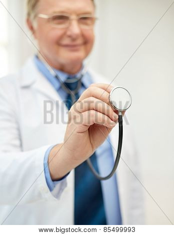 healthcare, profession, people and medicine concept - close up of happy doctor in white coat with stethoscope at medical office