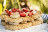 stock photo of french toast  - Tropical breakfast outdoor of French toast with bananas and strawberries - JPG