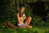 stock photo of stray dog  - A young beautiful woman with blonde hair is holding lovingly a stray dog in her arms sitting in a backyard garden with green grass - JPG