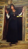pic of wicca  - A beautiful young woman with dark hair in a black velvet historical dress is standing at the door of a forest log cottage - JPG