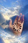 picture of roman numerals  - Hand in the clouds with a roman numeral clock on the palm - JPG