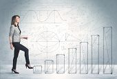 stock photo of climb up  - Business woman climbing up on hand drawn graphs concept on background - JPG