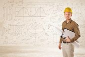 stock photo of engineer  - Handsome engineer calculating with hand drawn background concept - JPG