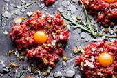 stock photo of tartar  - Beef tartare with pickled cucumber and fresh onion on dark marble background close - JPG