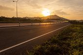 pic of cross hill  - road crosses rural landscape with the silhouette of hill on background the colors of a sunset - JPG