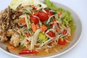 stock photo of green papaya salad  - papaya spicy salad with salmon on white table in restaurant