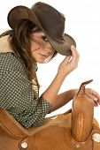 image of cowgirls  - a cowgirl with a serious expression on her face leaning on her saddle - JPG