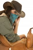 stock photo of cowgirls  - a cowgirl leaning on her saddle with a bandana on her face - JPG