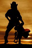 picture of western saddle  - a silhouette of a woman in her western wear holding on to her saddle - JPG