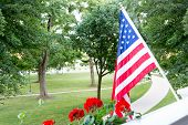 stock photo of balustrade  - American Stars and Stripes flag flying from a balcony or patio overlooking a park with trees in a patriotic gesture or to celebrate the 4th July and Independence Day - JPG