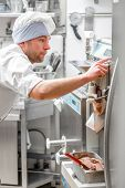 picture of confectioners  - Handsome confectioner in chef uniform producing ice cream with ice cream machine - JPG