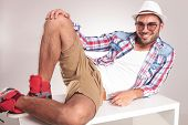 stock photo of knee-cap  - Young casual man resting on a white table - JPG