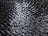 picture of cobblestone  - Fragment of wet road covered with dark cobblestone after the rain - JPG