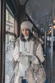 stock photo of tram  - Beautiful young woman wearing ecological fur while texting on a tram - JPG