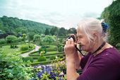 picture of retirement  - Portrait of a happy caucasian senior woman taking photo in a park - JPG