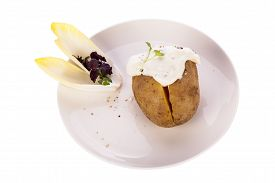 stock photo of endive  - Overhead view of a healthy oven baked jacket potato with sour cream sauce garnished with endive leaves and fresh herbs - JPG