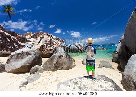 Little boy enjoying view of beautiful scenery of The Baths beach area major tourist attraction at Virgin Gorda, British Virgin Islands, Caribbean