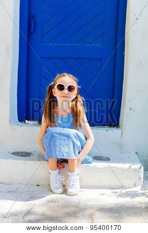 Charming little girl sitting outdoors in front of a blue door at typical greek traditional village on Mykonos Island, Greece, Europe