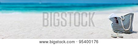 Bag, sun glasses and flip flops on a tropical beach. Wide panorama, perfect for banners