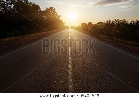 asphalt road to horizon in sunset