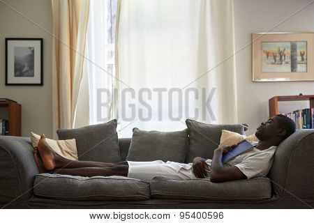 african black man sleeping on sofa couch while reading book at home living room lounge