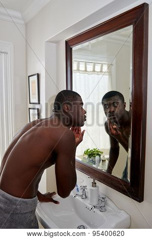 shirtless african black man checking for clean shave in mirror reflection in home bathroom