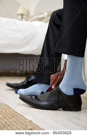 professional man getting ready for work putting formal smart shoes on for work in morning at home