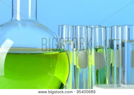 Laboratory glassware filled with colored liquids over blue background