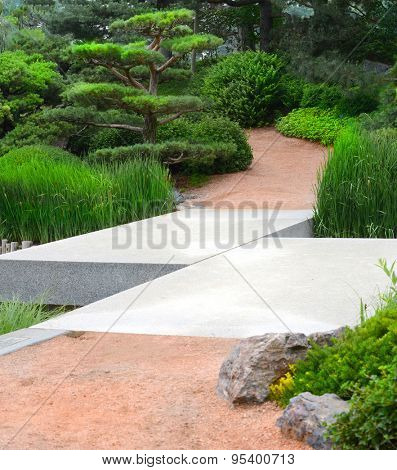 Zig-Zag bridge crossing over a stream leading to a Japanese Garden setting
