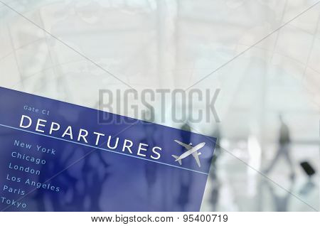 An airport departure board superimposed over an blurred airport scene with travellers and world map. The people are unrecognizable,