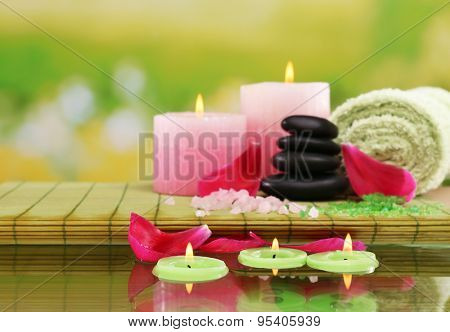 Spa still life with pink petals and candlelight on green blurred background