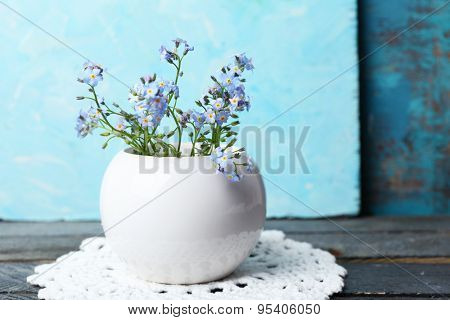 Composition with Forget-me-nots flowers on wooden background